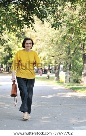 "Energic and smiling ""80 something"" senior woman walking in park on sunny day - stock photo"