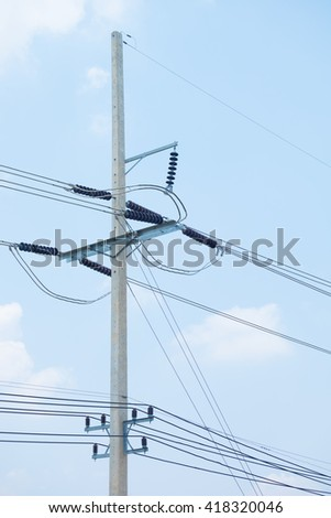 Energy and technology: electrical post by the road with power line cables, transformers and phone lines against sky background providing copy space. High voltage power pole on cloud and sky background - stock photo