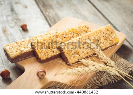 Energy bars, granola bars, muesli bars and wheat cereals on wooden cutting board. Selective focus - stock photo