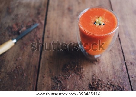 Energy booster; strawberry orange lemon and passion fruit smoothie on wooden working table. Selective focus on smoothie glass with copy space. - stock photo