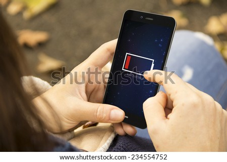energy concept: Female hands using smart phone with low battery - stock photo