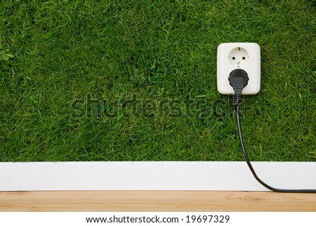 energy concept outlet in green wall - stock photo
