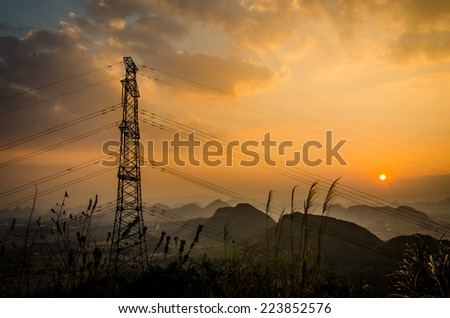 Energy Distribution Network - Electricity Pylons against Orange and Yellow Sunrise - stock photo