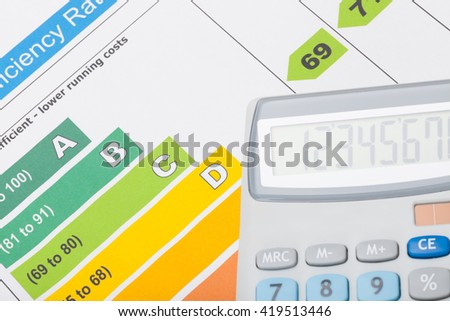 Energy efficiency chart and calculator over it - close up shot - stock photo