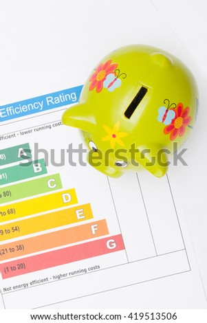 Energy efficiency chart and green color piggybank over it - view from top - stock photo