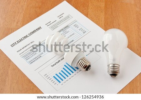 Energy efficient and incandescent  bulbs on electric bill. Energy efficient house concept. - stock photo