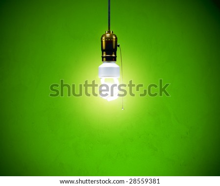Energy-efficient CFL bulb shining at center from a simple brass fixture. Green background slightly textured. - stock photo