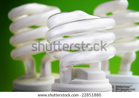energy efficient light bulbs on green background - stock photo