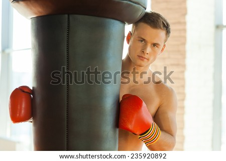 Energy inside me. Confident young boxer in sports gloves leaning at the punching bag and looking at camera - stock photo