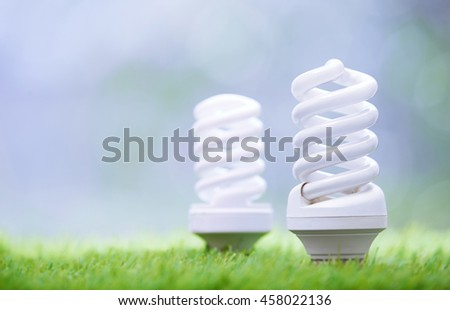 Energy saving bulbs in the grass. Close-up photo - stock photo