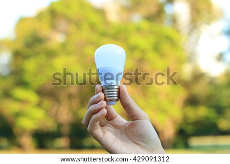 Energy saving concept. Hand holding light bulb on abstract nature background. - stock photo