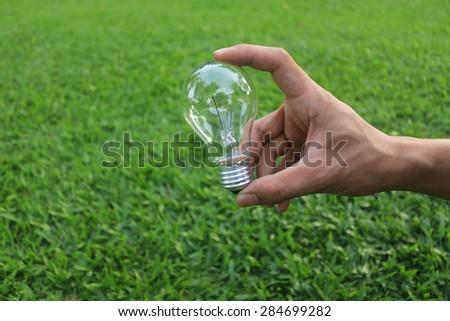 Energy saving concept. Hand holding light bulb on green grass background,. - stock photo