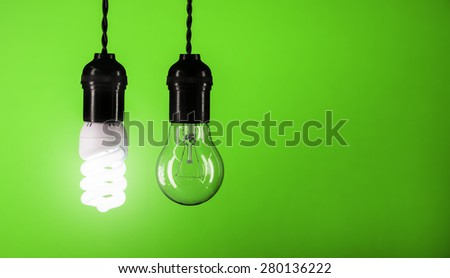 Energy saving concept of bulb over green background - stock photo