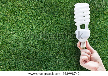 Energy saving concept, Woman hand holding light bulb on grass background,Ideas light bulb in the hand - stock photo