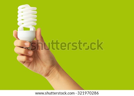 Energy saving concept. Woman hand holding light bulb on green background. - stock photo