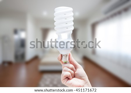 Energy saving concept, Woman hand holding light bulb on room house background,Ideas light bulb in the hand