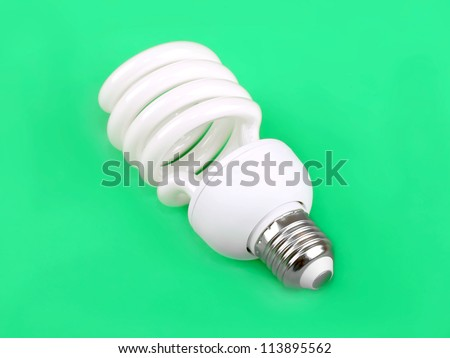 Energy saving fluorescent light bulb on green background - stock photo