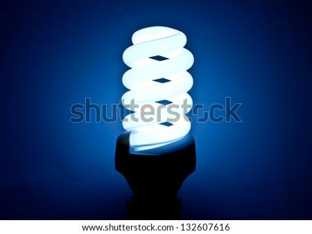 Energy Saving Lamp and blue background. - stock photo