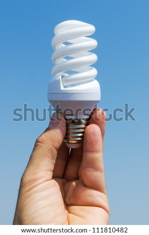 energy saving lamp in hand - stock photo
