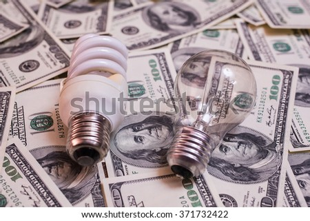 energy saving lamp, incandescent, fluorescent, energy saving, saving electricity, money background, Eco energy saving light bulb, comparison of energy saving lamps and incandescent lamps - stock photo