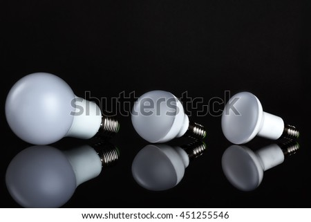 Energy saving lamp on black background. Sales of light bulbs. Advertising for energy-saving bulbs. Place for your text.
