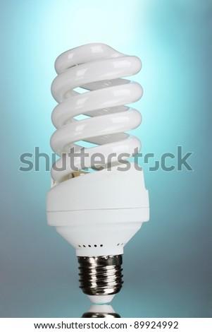 energy saving light bulb on blue background - stock photo