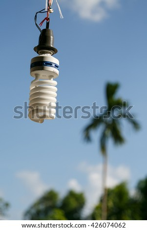 Energy saving light old bulbs with cap with ropes. blue sky and tree blur background,sunlight
