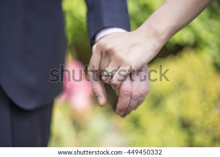 Engaged male and female hands showing off engagement ring in a romantic pose - stock photo