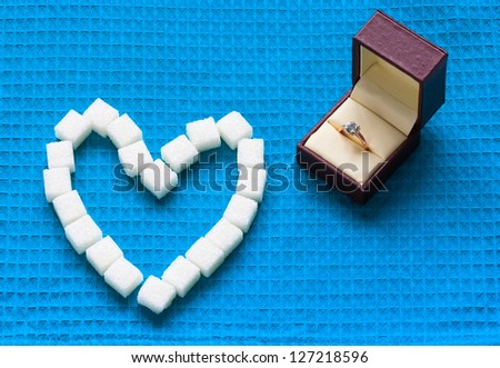 engagement ring and sugar hearts - stock photo
