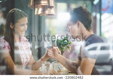 Engagement ring in cafe, shot through glass - stock photo