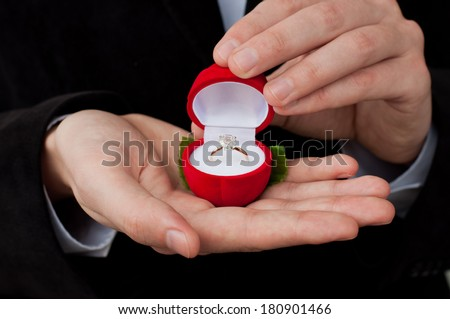 Engagement ring in hands. Man in suit holding an open box with engagement ring inside  - stock photo