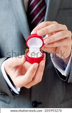 Engagement ring in hands. Man making proposal with wedding ring in open gift box - stock photo