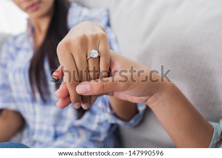 Engagement ring on womans hand held by her friend