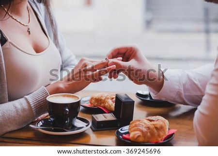 engagement ring, proposal in cafe, close up of hands of man and woman - stock photo