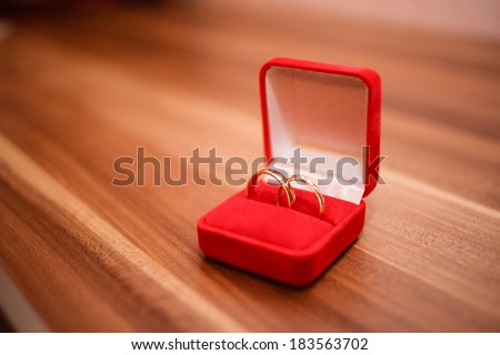 Engagement rings in red box on table. - stock photo