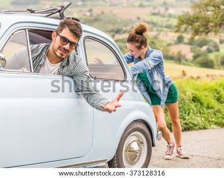 Engine break down.Strong young woman pushing a vintage car while man is emboldening her.Transportation, teamwork, funny concept - stock photo