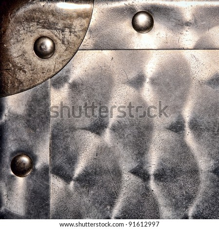 Engine turned finish type steel sheet metal grunge background with reinforcement corner and solid rivets featuring old scratches and dents on a container case - stock photo