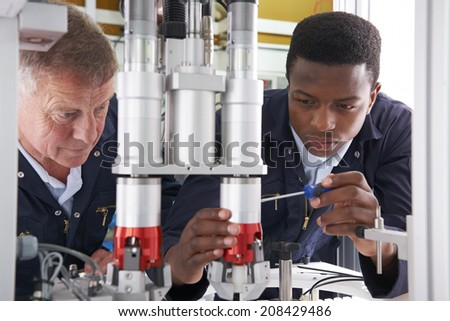 Engineer And Apprentice Working On Machine In Factory - stock photo