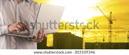 Engineer and architect hold digital laptop computer on sunset sky with clouds and sun background No face Unrecognizable person New highrise apartment buildings and construction cranes Silhouette Crane - stock photo