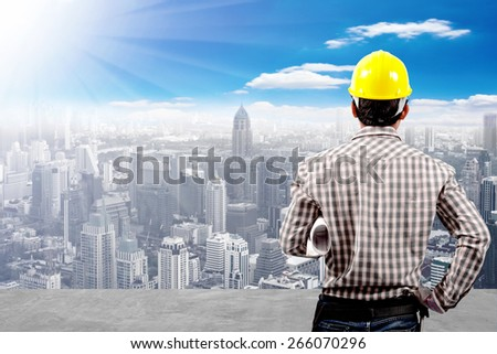 Engineer and blueprint working at high building construction site against blue sky with in concept ecology and real estate - stock photo