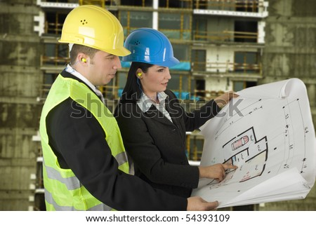 Engineer and client looking on project on the construction site - stock photo