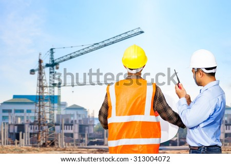 Engineer and foreman looking at blueprints use radio communication for command working against building construction crane  - stock photo