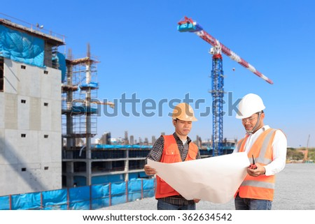 Engineer and foreman looking at plan for working control in construction site - stock photo