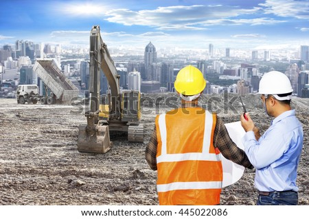 Engineer and Foreman looking plan for control working with excavator on a construction site against urban scene - stock photo