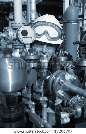 engineer and pipeline controls, close ups, inside oil and gas refinery, bluish toning idea