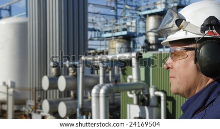 engineer and refinery in close-ups, pipelines and towers in background - stock photo