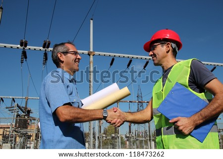 Engineer and Worker at Electrical Substation. Smiling workers with blueprints and clipboard in meeting at electrical substation. Electrical power industry. Electric power distribution - stock photo