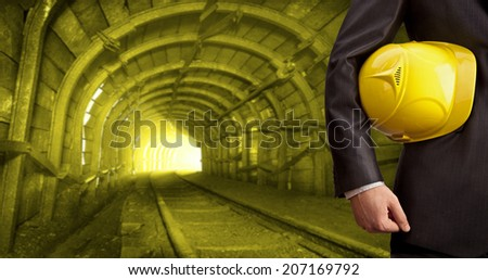 engineer and worker hand holding yellow helmet for workers security against background of an underground mine with arc legs and rails for trolleys with coal in perspective Copy space for inscription - stock photo