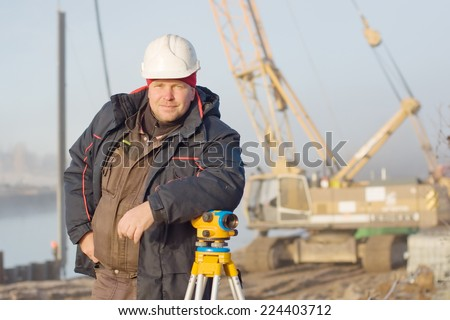 Engineer at the construction site makes measurements with leveling - stock photo