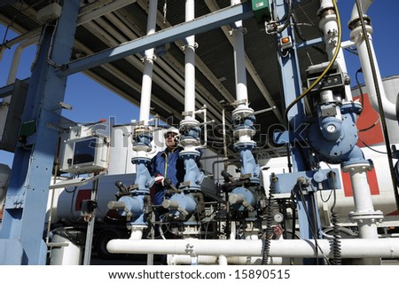 engineer behind pipelines at large fuel depot inside oil and gas refinery - stock photo